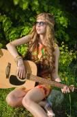 フィールドの上に座って、ギターを演奏若い女性 — ストック写真