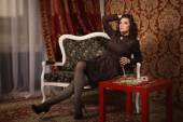 Bir siyah elbise oturma iyon kanepede kadında — Stok fotoğraf