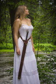Beautiful woman in white dress with sword in a wild forest — Stock Photo