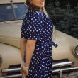 Lady in vintage dress standing near retro car — Stock Photo #82757644