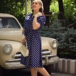Lady in vintage dress standing near retro car — Stock Photo #82757550