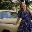 Lady in vintage dress standing near retro car — Stock Photo #82757832