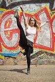 Chica joven bailando sobre fondo de graffiti — Foto de Stock