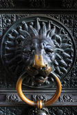 Ancient metal lion head on the door to catholic church — Stock Photo