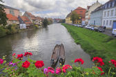 River, boats, red flowers and vintage houses — Stock Photo