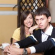 Young couple sit near table in coffee shop. — Stock Photo #68700617