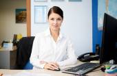Young pretty business woman at workplace in office — Stock Photo