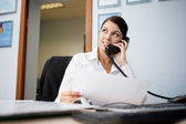 Portrait of young businesswoman talking on phone in office — Stock Photo