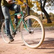 Close-up of young man riding bicycle in park — Stock Photo #57932005
