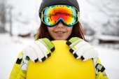 Beautiful young woman posing outdoors with her snowboarding gear — Stock Photo