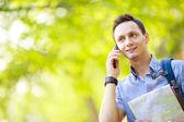 Homem segurando o mapa ao ar livre e falando por telefone — Fotografia Stock