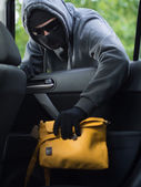 Transportation crime concept .Thief stealing bag from the car — Stock Photo