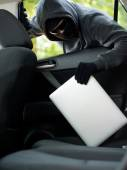 Car theft - a laptop being stolen through the window of an unoccupied car. — Stock Photo