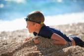 The boy lies on a pebble beach after swimming — Stock Photo