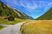 Wide dirt road in an Alpine valley — Stock Photo
