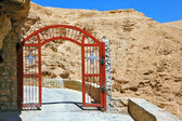 The gate with a cross on a mountain road  — Stock Photo
