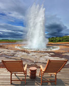 Geyser Strokkur in Iceland with  chairs and table — Stock Photo