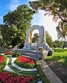 The arch frames the bronze statue of Johann Strauss — Stockfoto