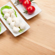 Tomatoes, mozzarella and green salad leaves — Stock Photo #52438815