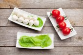 Tomatoes, mozzarella and green salad leaves — Stock Photo