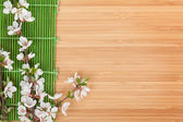 Sakura branch over bamboo mat — Foto Stock