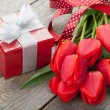 Fresh red tulips with gift box — Stock Photo