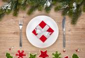 Gift box on plate and silverware — Stock Photo