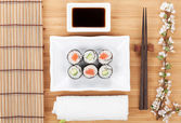 Sushi maki set with sakura branch — Stock Photo