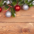 Christmas fir tree with snow and baubles on rustic wooden board — Stok fotoğraf #55359081