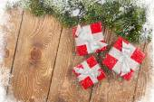Old wood texture with snow, gift boxes and firtree — Stock Photo