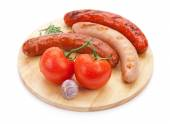 Grilled sausages with condiments and tomatoes — Stock Photo