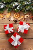 Gift boxes over christmas wooden background — Stock Photo