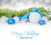 Christmas baubles and blue ribbon with snow fir tree — Foto Stock