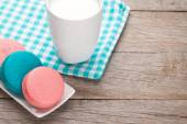 Colorful macaron cookies and cup of milk — Stock Photo