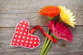 Colorful gerbera flowers and heart toy — Stock Photo