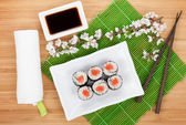 Sushi maki set and sakura branch — Stock Photo