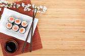 Sushi maki with salmon and sakura branch — Stock Photo