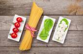 Tomatoes, mozzarella, pasta and green salad leaves — Stock Photo