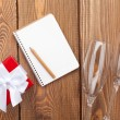 Blank notepad, gift box and champagne glasses — Stock Photo #61640515