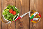 Tape measure and healthy food — Stock Photo