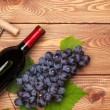 Red wine bottle and bunch of red grapes — Stock Photo #64036941