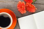 Lege Kladblok, koffiekopje en oranje gerbera 's — Stockfoto
