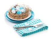 Easter eggs nest on plate with silverware — Stock Photo
