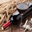 Glass of red wine, bottle and corkscrew — Stock Photo #65350035
