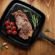 Sirloin steak with rosemary and cherry tomatoes on frying pan — Stock Photo #66384387