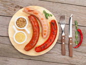 Grilled sausages with condiments — Stock Photo