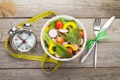 Fresh healthy salad and measuring tape — Stock Photo