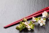 Japanese sushi chopsticks and sakura blossom — Stock Photo