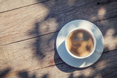 Coffee cup on sunny garden table — Stock Photo