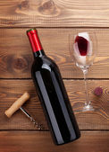 Red wine bottle, glass and corkscrew — Stock Photo